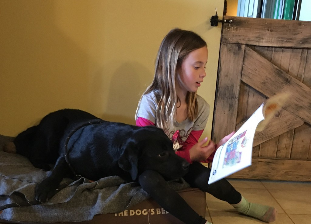 Girl reading to our school dog Joy (a black lab)